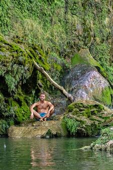 Garçon méditant sous la cascade immergé dans la nature
