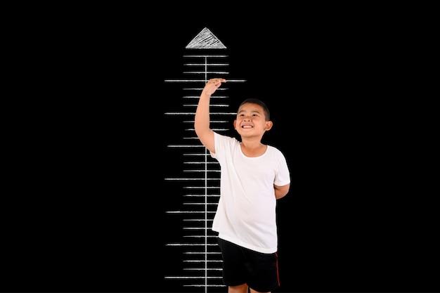Le garçon a mesuré la hauteur avec le tableau noir