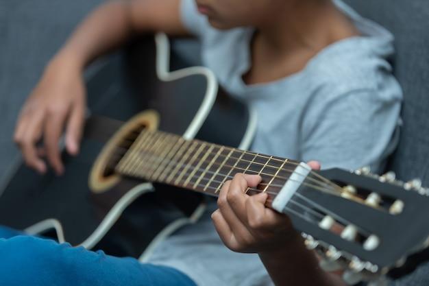 Garçon mexicain jouant de la guitare à la maison, l'enseignement à domicile