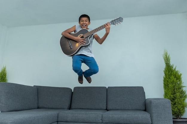 Garçon mexicain sautant du canapé et jouant de la guitare