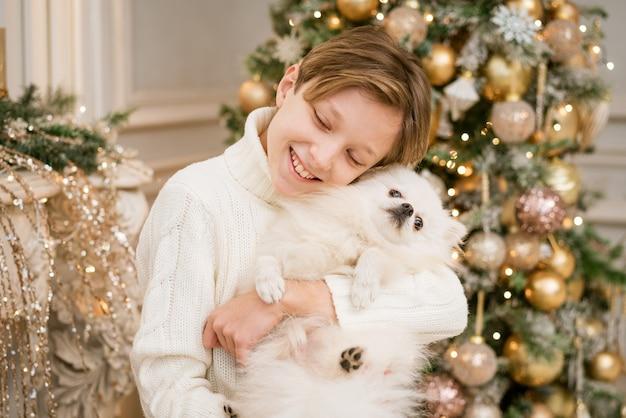 Garçon mignon à l'arbre de noël avec un chien en prévision de joyeux noël garçon heureux et chien embrasse son te...