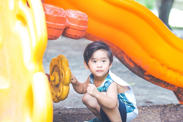 Garçon mignon asiatique joue dans la cour de récréation.
