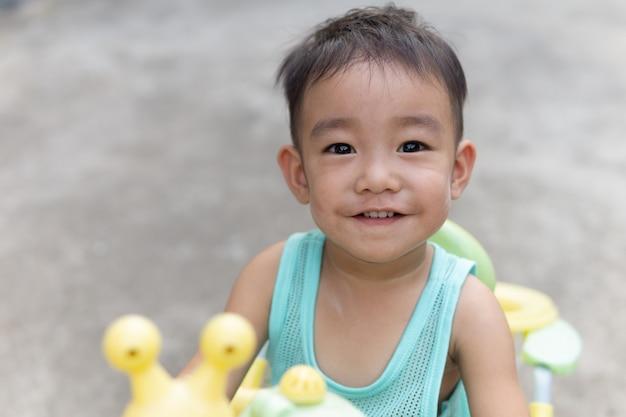 Garçon mignon asiatique souriant et regardant la caméra. portrait d'enfants assis sur son vélo.