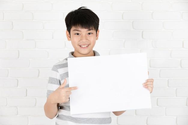 Garçon mignon asiatique tenant un tableau blanc blanc.