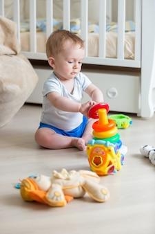 Garçon mignon assemblant la pyramide colorée sur le plancher au salon