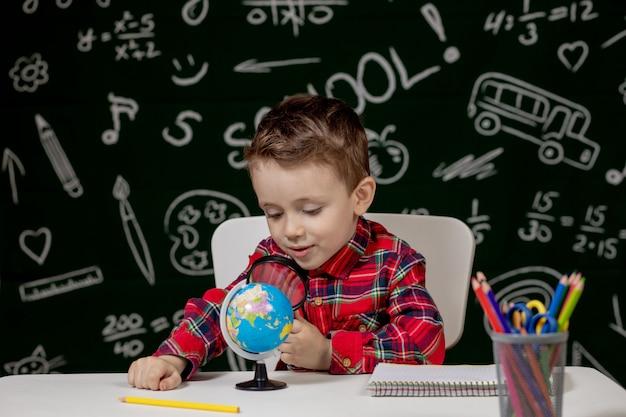 Garçon mignon assis à un bureau avec une loupe à la main