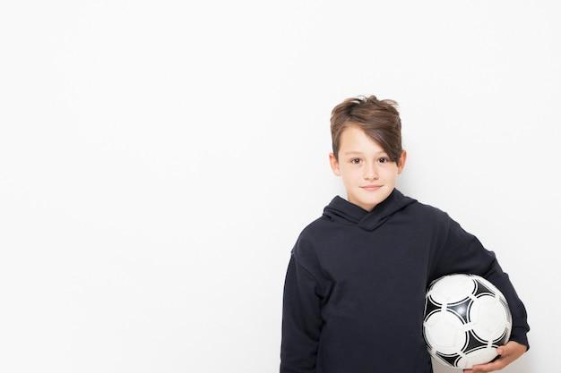 Garçon mignon avec un ballon de football dans ses mains sur un fond blanc