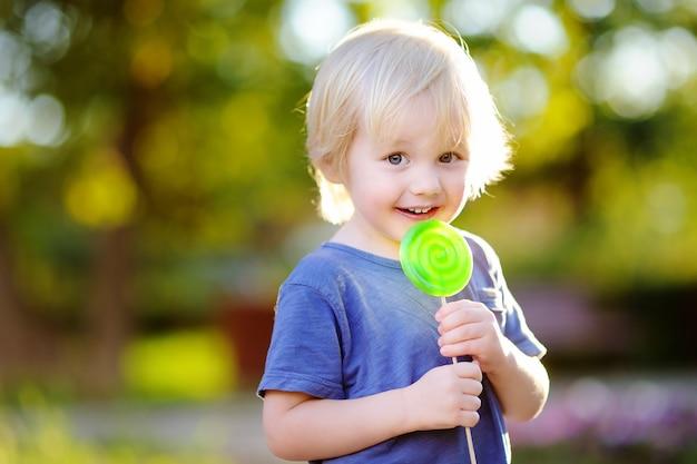 Garçon mignon bambin avec grosse sucette verte. enfant mangeant des friandises sucrées. bonbons pour les jeunes enfants. plaisirs d'été en plein air