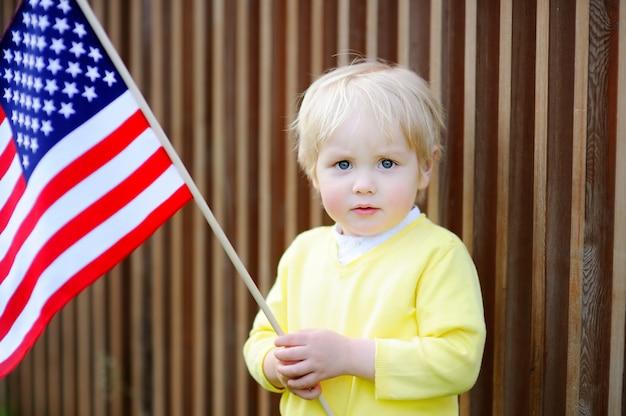 Garçon mignon bambin tenant le drapeau américain.