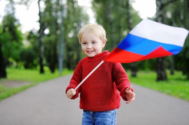 Garçon mignon bambin tenant le drapeau russe à l'extérieur