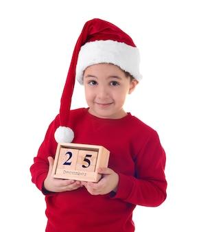 Garçon mignon en bonnet de noel avec calendrier. notion de compte à rebours de noël
