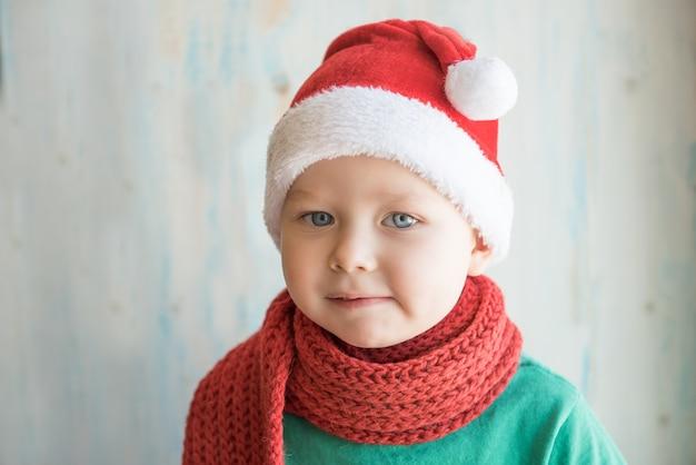 Garçon mignon en bonnet de noel et écharpe rouge