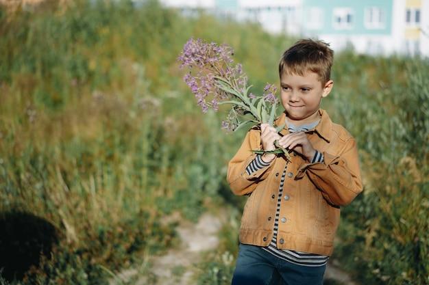 Garçon mignon sur la clairière des marguerites sauvages avec un bouquet de fleurs d'épilobe