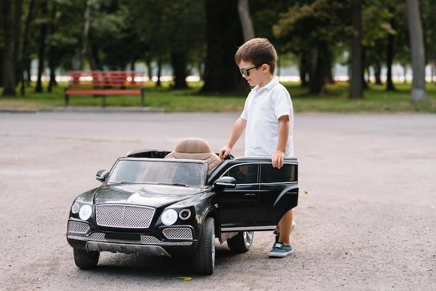 Garçon mignon à conduire une voiture électrique noire dans le parc