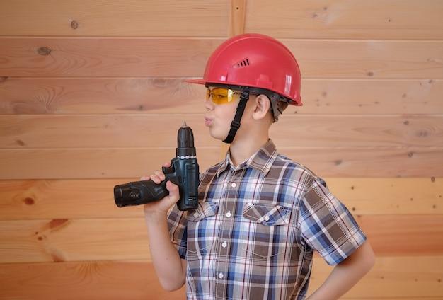 Garçon mignon dans un casque de construction et des lunettes avec un tournevis dans ses mains à l'intérieur d'une maison en bois. construction et décoration de maisons en bois
