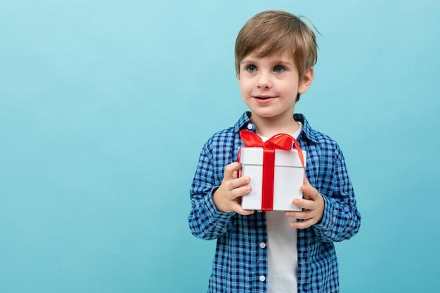 Garçon mignon dans une chemise à carreaux détient un cadeau sur un bleu clair avec fond