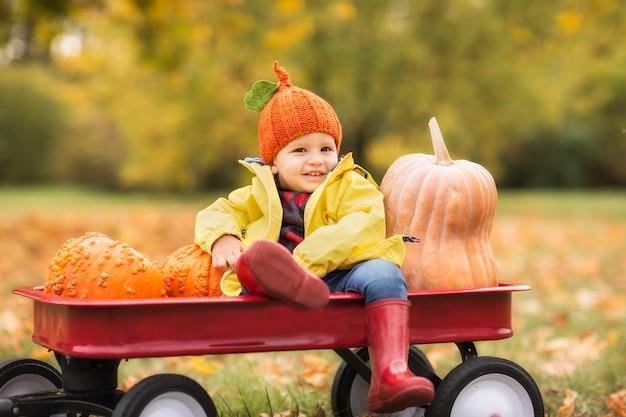 Garçon mignon dans un imperméable jaune, bottes en caoutchouc rouge dans le parc en automne