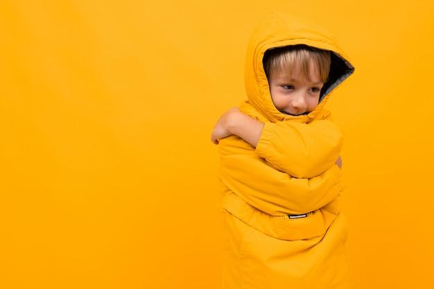 Un garçon mignon dans un sweat à capuche jaune s'est étreint et était timide