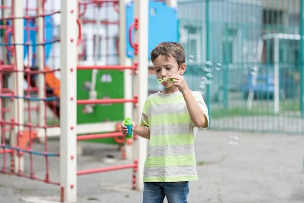 Garçon mignon dans un tshirt rayé soufflant des bulles sur une aire de jeux