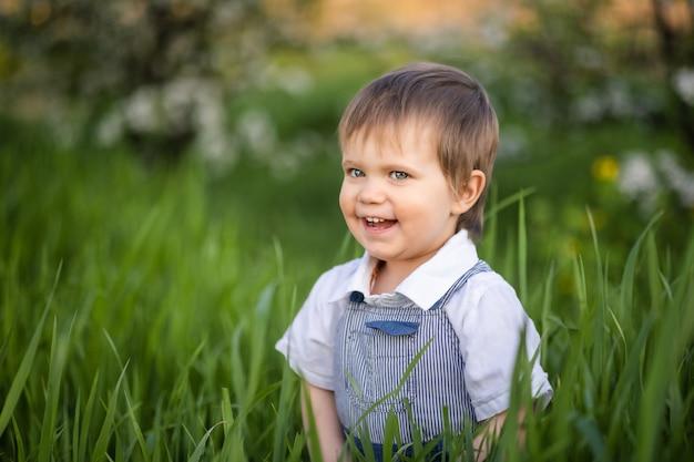 Garçon mignon dans des vêtements à la mode aux yeux bleus joue et saute dans les hautes herbes dans un grand jardin fleuri vert