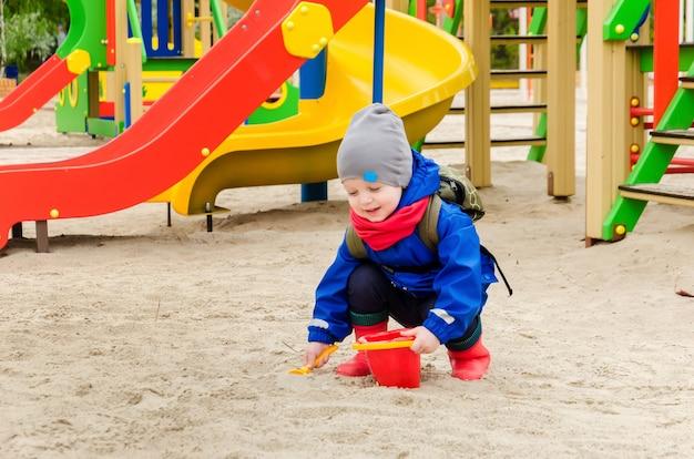 Garçon mignon de deux ans dans une veste bleue et une écharpe rouge joue sur une aire de jeux lumineuse avec une cuillère et un seau