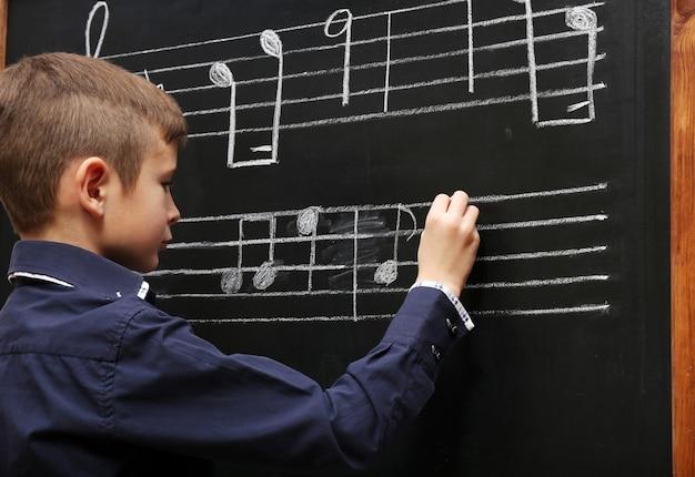 Garçon mignon écrivant au tableau noir avec des notes de musique, dans la salle de classe