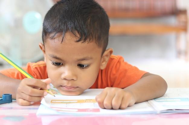 Garçon mignon d'enfant étudiant et pensant à la maison.