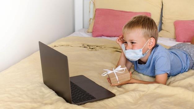 Un garçon mignon félicite via un lien vidéo et donne un cadeau