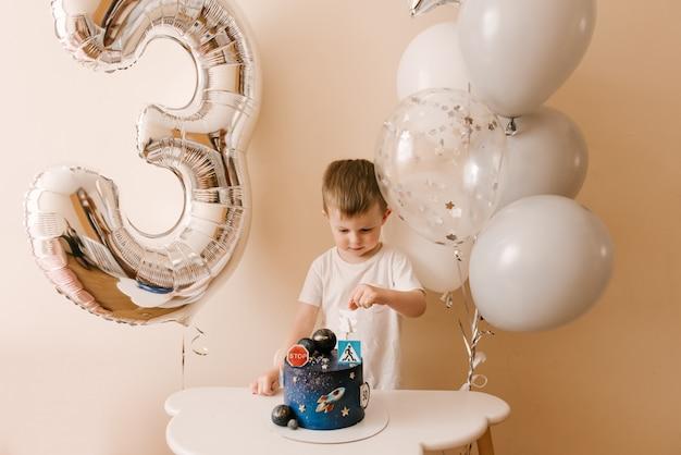 Garçon mignon fête son anniversaire et mange un délicieux beau gâteau, photo d'un enfant avec des ballons
