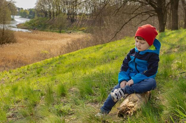 Garçon mignon un garçon de quatre ans est assis sur une colline sur une bûche et regarde le lac. tourisme vert en famille, marcher avec des enfants en plein air