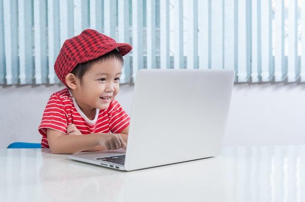Garçon mignon jouant au labtop dans la chambre des enfants