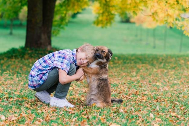 Garçon mignon jouant et marchant avec son chien dans un pré.