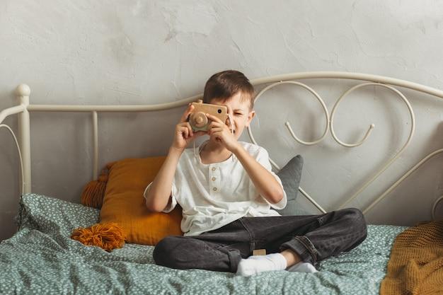 Un garçon mignon joue au photographe avec un appareil photo en bois jouet
