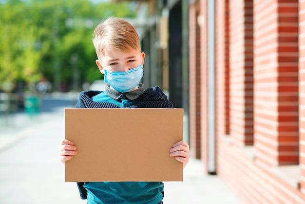 Garçon mignon portant le visage mak. enfant tenant un plateau vide. le garçon veut revenir à la vie normale.