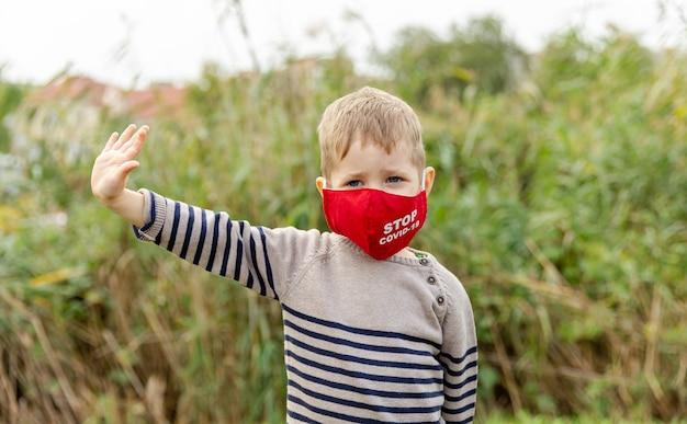 Un garçon mignon protège la propagation du virus de la maladie avec un masque
