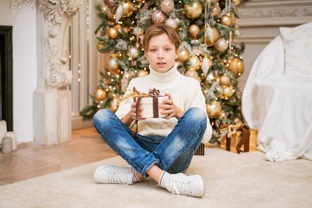 Un garçon mignon en pull est assis près de l'arbre de noël avec des cadeaux, un adolescent caucasien à la maison avec des...