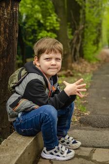 Garçon mignon quatre ans de marche dans le parc au début du printemps. l'enfant s'assit pour se reposer après une longue promenade fascinante.