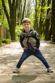 Garçon mignon quatre ans de marche dans le parc au début du printemps.