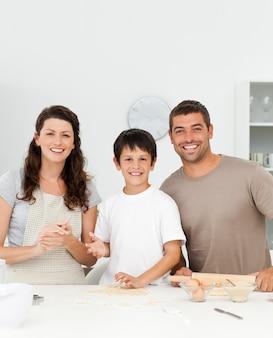 Garçon mignon avec ses parents dans sa cuisine