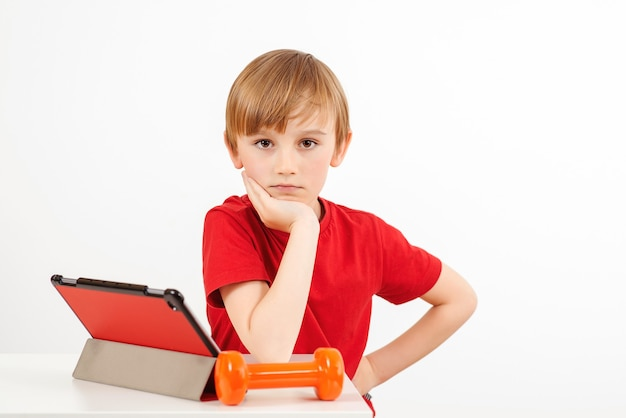 Garçon mignon avec tablette faisant des exercices de sport à la maison.