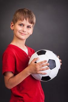 Garçon Mignon Tenant Un Ballon De Football Photo Premium