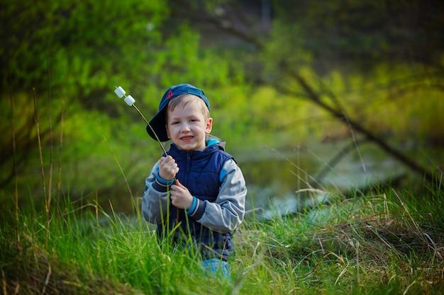 Garçon mignon tenant un bâton et prêt à manger des guimauves grillées
