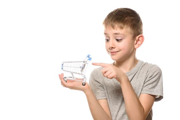 Garçon mignon tient un petit caddie en métal dans la main et le pointe avec l'index. isoler sur fond blanc. concept de magasinage.