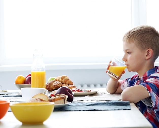 Garçon mignon avec un verre de jus