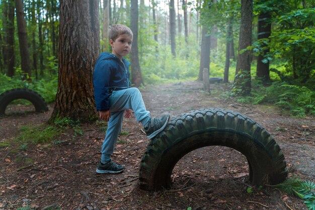 Garçon a mis son pied sur la roue. joue dans le parc et fait du sport
