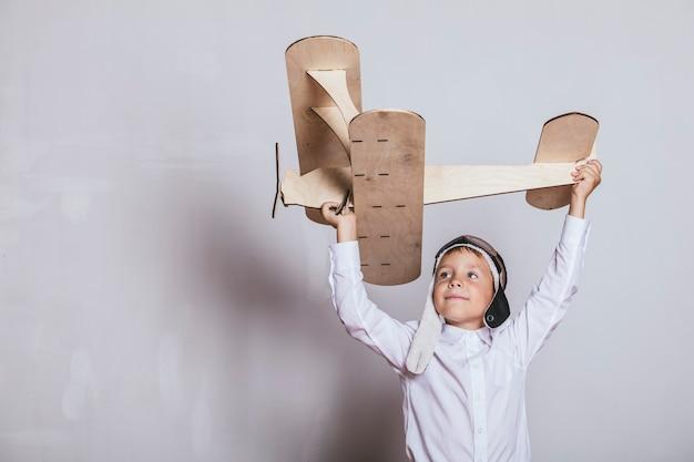 Garçon avec modèle d'avion en bois et une casquette avec capuchon