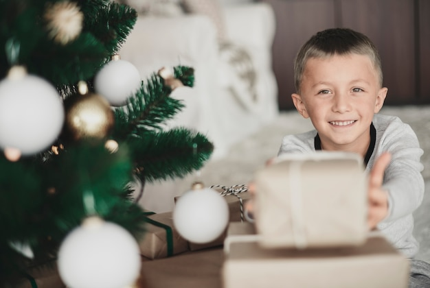 Garçon montrant un cadeau de noël à la caméra