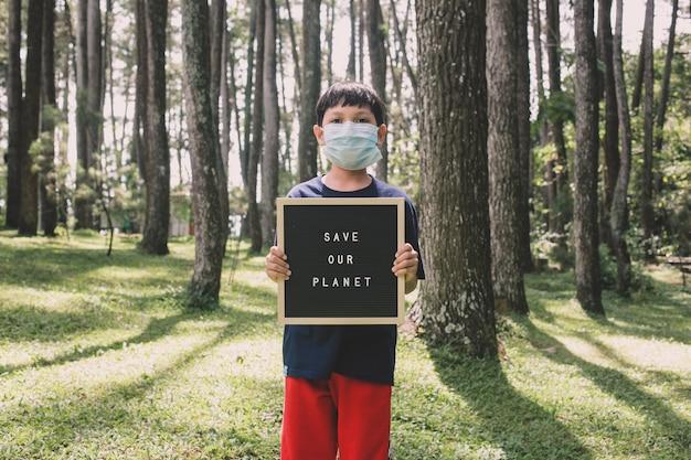 Un garçon montrant une citation sur un tableau à lettres dit sauver notre planète avec la forêt