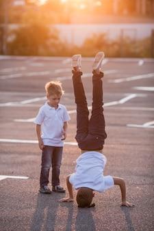 Le garçon montre un poirier dans la rue. le jeune frère admire son frère
