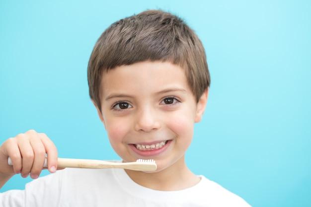 Garçon montrer les dents avec une brosse sur fond bleu